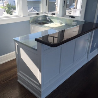 Seated home bar - traditional l-shaped dark wood floor seated home bar idea in Philadelphia with a drop-in sink, shaker cabinets, white cabinets and granite countertops
