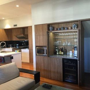 Esempio di un piccolo angolo bar minimalista con ante in stile shaker, ante in legno scuro, top in superficie solida e pavimento in legno massello medio