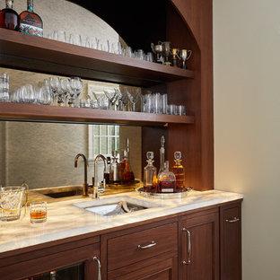 グランドラピッズのトラディショナルスタイルのおしゃれなウェット バー (I型、アンダーカウンターシンク、中間色木目調キャビネット、オニキスカウンター、ミラータイルのキッチンパネル、無垢フローリング) の写真