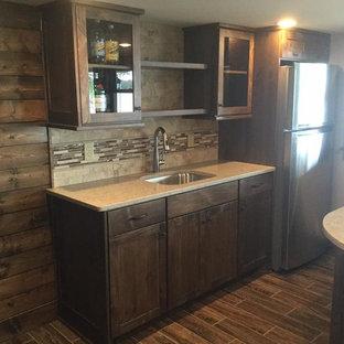 Immagine di un piccolo armadio bar stile americano con lavello sottopiano, ante lisce, ante in legno bruno, top in quarzo composito, paraspruzzi beige, paraspruzzi in travertino, pavimento in gres porcellanato, pavimento marrone e top beige
