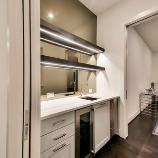 Inspiration for a medium sized contemporary single-wall wet bar in Houston with a submerged sink, recessed-panel cabinets, white cabinets, quartz worktops, black splashback, glass sheet splashback, dark hardwood flooring, brown floors and white worktops.