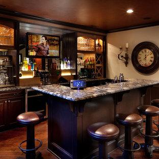 コロンバスのトラディショナルスタイルのおしゃれな着席型バー (濃色無垢フローリング、ll型、レイズドパネル扉のキャビネット、濃色木目調キャビネット、茶色い床、マルチカラーのキッチンカウンター) の写真