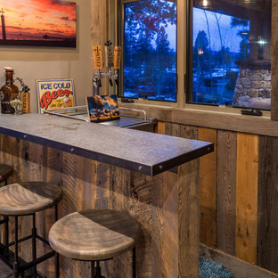 Example of a small mountain style l-shaped seated home bar design in Other with distressed cabinets and stainless steel countertops