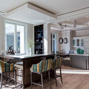 Ispirazione per un piccolo bancone bar tropicale con ante in legno bruno, parquet chiaro e pavimento beige