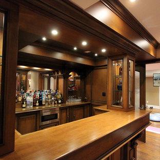 トロントの大きいトラディショナルスタイルのおしゃれな着席型バー (L型、ドロップインシンク、家具調キャビネット、茶色いキャビネット、木材カウンター、茶色いキッチンパネル、木材のキッチンパネル、ラミネートの床、茶色い床) の写真