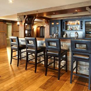 トロントの中くらいのラスティックスタイルのおしゃれな着席型バー (無垢フローリング、木材カウンター、ll型、ガラス扉のキャビネット、ヴィンテージ仕上げキャビネット、茶色い床、茶色いキッチンカウンター) の写真