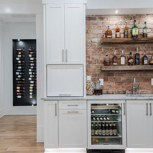 Photo of a medium sized rural wet bar in Raleigh with a submerged sink, shaker cabinets, white cabinets, marble worktops, red splashback, brick splashback, light hardwood flooring and beige floors.