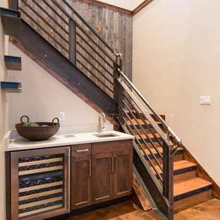 Inspiration for a small rustic single-wall linoleum floor and brown floor wet bar remodel in Denver with an undermount sink, shaker cabinets, dark wood cabinets and solid surface countertops