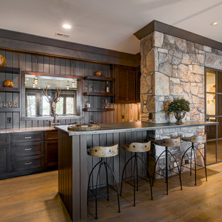 Example of a mountain style medium tone wood floor seated home bar design in Other with open cabinets and dark wood cabinets