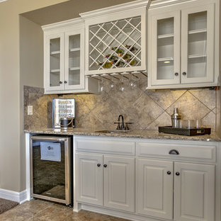 Photo of a medium sized classic single-wall wet bar in Kansas City with a submerged sink, raised-panel cabinets, white cabinets, beige splashback and brown floors.