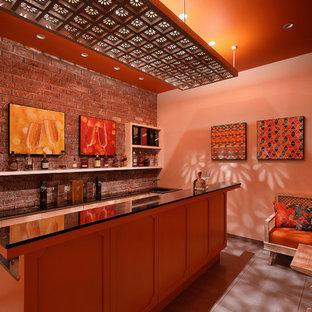 アフマダーバードのアジアンスタイルのおしゃれなウェット バー (ll型、ドロップインシンク、落し込みパネル扉のキャビネット、オレンジのキャビネット、茶色いキッチンパネル、レンガのキッチンパネル、グレーの床、黒いキッチンカウンター) の写真
