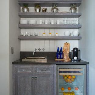 オレンジカウンティの小さいトランジショナルスタイルのおしゃれなウェット バー (I型、シェーカースタイル扉のキャビネット、グレーのキャビネット、濃色無垢フローリング、ドロップインシンク、クオーツストーンカウンター、白いキッチンパネル、茶色い床) の写真