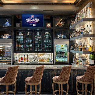 Immagine di un grande bancone bar tradizionale con lavello sottopiano, ante di vetro, ante con finitura invecchiata, top in granito e paraspruzzi in lastra di pietra