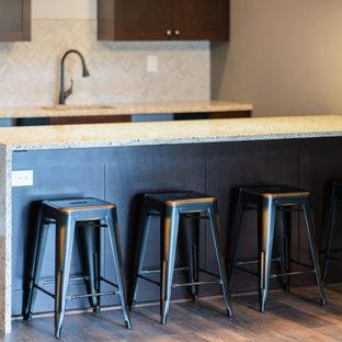 ルイビルのおしゃれなウェット バー (I型、ドロップインシンク、落し込みパネル扉のキャビネット、濃色木目調キャビネット、テラゾーカウンター、グレーのキッチンパネル、石タイルのキッチンパネル、無垢フローリング、茶色い床、ベージュのキッチンカウンター) の写真