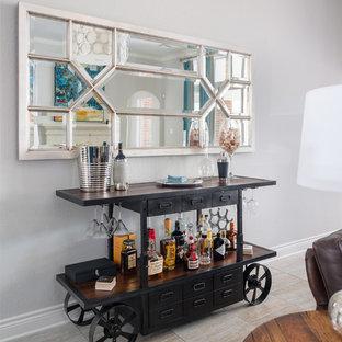Idee per un carrello bar tradizionale con ante nere, top in legno, pavimento beige e top marrone