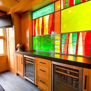 バンクーバーのラスティックスタイルのおしゃれな着席型バー (ll型、落し込みパネル扉のキャビネット、中間色木目調キャビネット、テラゾーカウンター、磁器タイルの床) の写真