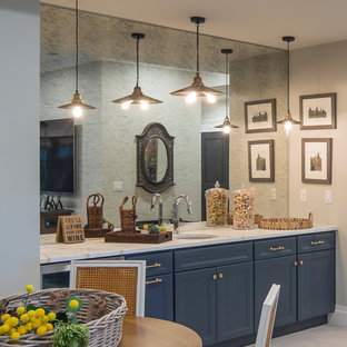 Inspiration for a medium sized traditional single-wall wet bar in Dallas with a submerged sink, recessed-panel cabinets, blue cabinets, marble worktops, mirror splashback, concrete flooring, grey floors and white worktops.