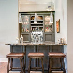 Esempio di un bancone bar chic di medie dimensioni con lavello sottopiano, ante con riquadro incassato, ante grigie, top in granito, paraspruzzi grigio, paraspruzzi con piastrelle a mosaico e pavimento in legno massello medio
