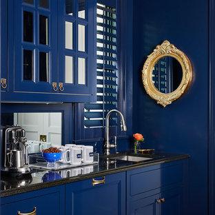 Idee per un angolo bar con lavandino chic con lavello sottopiano, ante con riquadro incassato, ante blu, paraspruzzi a specchio e top nero