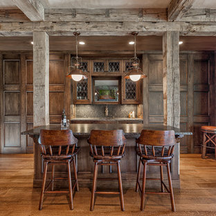 Inspiration for a large rustic galley breakfast bar in Other with granite worktops, medium hardwood flooring, dark wood cabinets, grey splashback, a submerged sink, glass-front cabinets, stone slab splashback and brown floors.