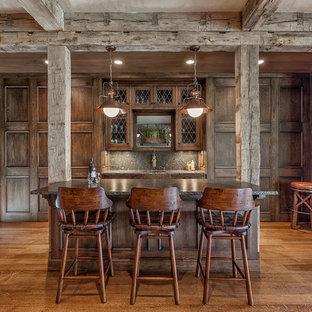 他の地域の広いラスティックスタイルのおしゃれな着席型バー (御影石カウンター、無垢フローリング、濃色木目調キャビネット、グレーのキッチンパネル、ll型、アンダーカウンターシンク、ガラス扉のキャビネット、石スラブのキッチンパネル、茶色い床) の写真