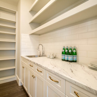 Inspiration for a medium sized contemporary single-wall wet bar in Calgary with a built-in sink, open cabinets, white cabinets, marble worktops, white splashback, ceramic splashback, dark hardwood flooring and brown floors.