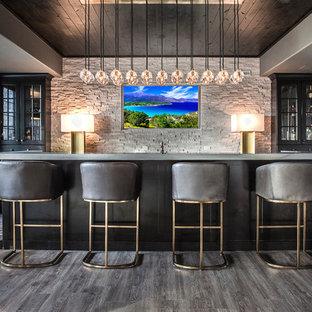Inspiration for a modern galley breakfast bar in Chicago with glass-front cabinets, black cabinets, concrete worktops, grey splashback, stone tiled splashback, dark hardwood flooring, grey floors and grey worktops.