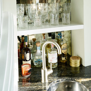 Inspiration for a classic home bar in Los Angeles with a submerged sink, white cabinets, granite worktops, black splashback, glass tiled splashback and light hardwood flooring.