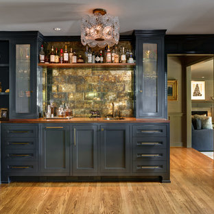 Large elegant l-shaped medium tone wood floor and brown floor wet bar photo in Portland with a drop-in sink, shaker cabinets, gray cabinets, wood countertops, metal backsplash and brown countertops