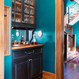 Esempio di un angolo bar con lavandino tradizionale con nessun lavello, ante di vetro, ante nere, top in legno, paraspruzzi a specchio, pavimento in legno massello medio e top marrone
