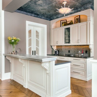 Inspiration for a traditional wet bar in Other with raised-panel cabinets, white cabinets and grey splashback.