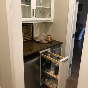 Inspiration for a small traditional single-wall wet bar in Other with no sink, glass-front cabinets, white cabinets, copper worktops, dark hardwood flooring, brown floors and brown worktops.