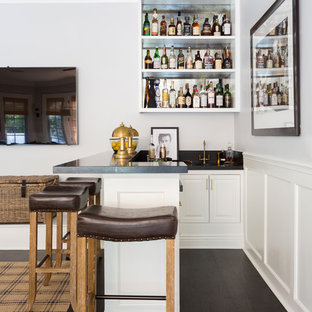 Mid-sized transitional l-shaped dark wood floor and brown floor seated home bar photo in Los Angeles with an undermount sink, open cabinets, white cabinets, granite countertops and black countertops