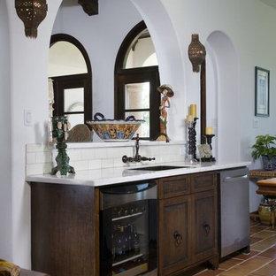 Foto di un armadio bar mediterraneo di medie dimensioni con lavello sottopiano, ante con bugna sagomata, ante in legno bruno, paraspruzzi bianco, paraspruzzi con piastrelle diamantate, pavimento in terracotta e pavimento marrone