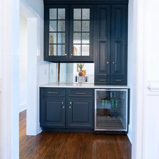 Foto di un piccolo angolo bar senza lavandino classico con ante in stile shaker, ante nere, top in quarzo composito, paraspruzzi a specchio, parquet scuro, pavimento marrone e top bianco