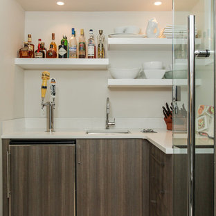 Home bar - small contemporary l-shaped home bar idea in Edmonton with an undermount sink, flat-panel cabinets, dark wood cabinets and white countertops