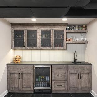 Exemple d'un bar de salon linéaire chic de taille moyenne avec un bar à boissons, une crédence blanche, une crédence en bois, un sol noir, un plan de travail noir, des portes de placard en bois brun, un évier encastré, un placard avec porte à panneau encastré, un plan de travail en stéatite et un sol en ardoise.
