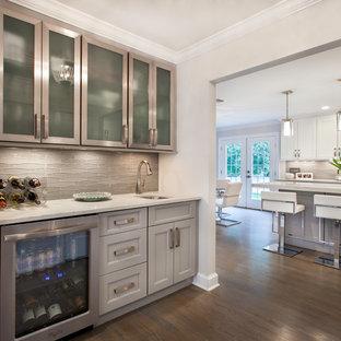 ニューヨークの小さいトランジショナルスタイルのおしゃれなウェット バー (アンダーカウンターシンク、落し込みパネル扉のキャビネット、グレーのキャビネット、クオーツストーンカウンター、グレーのキッチンパネル、ガラスタイルのキッチンパネル、I型、濃色無垢フローリング、茶色い床、白いキッチンカウンター) の写真