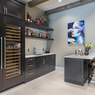 ダラスのトランジショナルスタイルのおしゃれな着席型バー (落し込みパネル扉のキャビネット、グレーのキャビネット、クオーツストーンカウンター、ベージュキッチンパネル、セラミックタイルのキッチンパネル、ライムストーンの床、ベージュの床、白いキッチンカウンター) の写真
