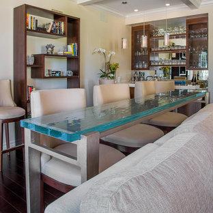 ロサンゼルスの広いミッドセンチュリースタイルのおしゃれな着席型バー (I型、オープンシェルフ、濃色木目調キャビネット、ミラータイルのキッチンパネル、濃色無垢フローリング、大理石カウンター、茶色い床、白いキッチンカウンター) の写真
