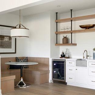 ミネアポリスのトランジショナルスタイルのおしゃれなウェット バー (I型、クオーツストーンカウンター、白いキッチンパネル、塗装板のキッチンパネル、淡色無垢フローリング、ベージュの床、白いキッチンカウンター) の写真