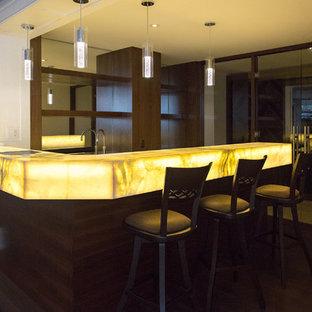 トロントの広いコンテンポラリースタイルのおしゃれな着席型バー (濃色無垢フローリング、茶色い床、アンダーカウンターシンク、オープンシェルフ、茶色いキャビネット、オニキスカウンター、ミラータイルのキッチンパネル、L型、黄色いキッチンカウンター) の写真