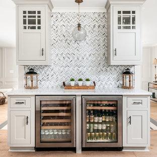 アトランタのトランジショナルスタイルのおしゃれなホームバー (I型、シンクなし、シェーカースタイル扉のキャビネット、グレーのキャビネット、マルチカラーのキッチンパネル、無垢フローリング、白いキッチンカウンター) の写真