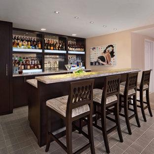 Ispirazione per un bancone bar tradizionale con lavello sottopiano, ante lisce, ante in legno bruno, top in onice, pavimento con piastrelle in ceramica, paraspruzzi a specchio e pavimento grigio