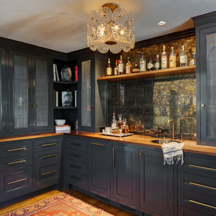 Inspiration for a transitional l-shaped wet bar remodel in Portland with a drop-in sink, recessed-panel cabinets, blue cabinets, wood countertops, mirror backsplash and brown countertops