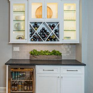 インディアナポリスのトランジショナルスタイルのおしゃれなホームバー (I型、シンクなし、ガラス扉のキャビネット、白いキャビネット、グレーのキッチンパネル、サブウェイタイルのキッチンパネル、無垢フローリング、黒いキッチンカウンター) の写真
