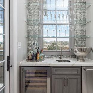 ダラスのトラディショナルスタイルのおしゃれなウェット バー (I型、アンダーカウンターシンク、落し込みパネル扉のキャビネット、グレーのキャビネット、白い床、白いキッチンカウンター) の写真