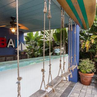 タンパの広いビーチスタイルのおしゃれなウェット バー (I型、ドロップインシンク、木材カウンター、レンガの床、グレーの床、青いキッチンカウンター) の写真