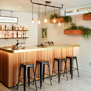 Example of an urban l-shaped gray floor seated home bar design in London with white backsplash and subway tile backsplash