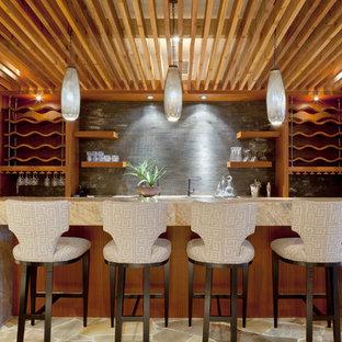 Esempio di un bancone bar tropicale con ante in legno scuro, paraspruzzi grigio e paraspruzzi con piastrelle in pietra